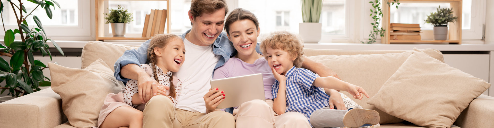 Young joyful casual family of two kids and couple sitting on sofa